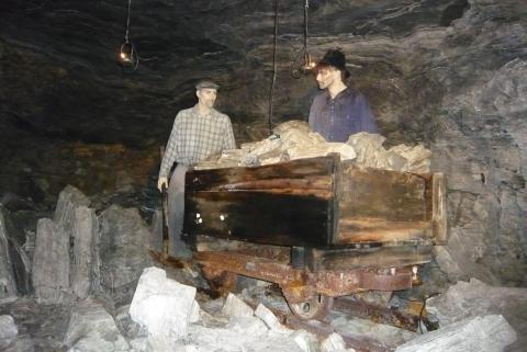 Gipsarbeiter mit Lore im Stollen
